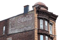 Surviving Coca-Cola signage atop older signage for clothing, Passaic, New Jersey