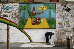 Touching up the wall outside Taste the Tropics, Flatbush, Brooklyn