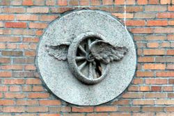 Winged wheel bas relief at the former Jubilee Garage, Morrisania, Bronx