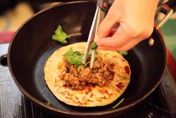 Adding chili pepper to beef keema paratha, Myanmar Baptist Church Fun Fair, East Elmhurst, Queens