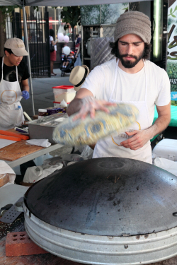 Applying flatbread to saj, Manousheh, Arab-American and North African Cultural Street Festival, Great Jones Street, Manhattan