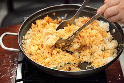 Preparing black goat fried rice, Bangane, Murray Hill, Queens