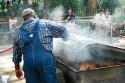 Ed Mitchell checks the progress of a hog at The Pit, at the Big Apple Barbecue