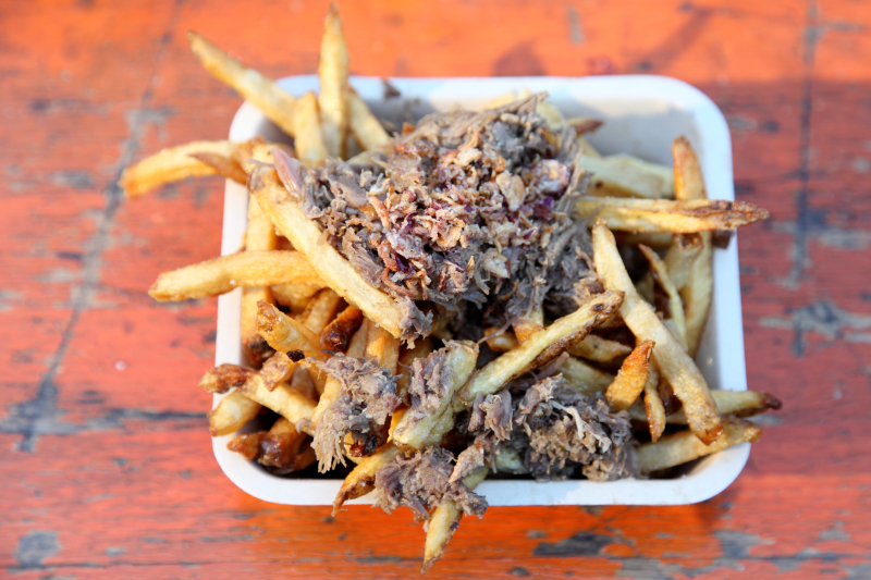 Duck-fat fries topped with duck confit  duck demi-glace  and fried shallots  Duck Season  Columbus Circle Holiday Market  Manhattan