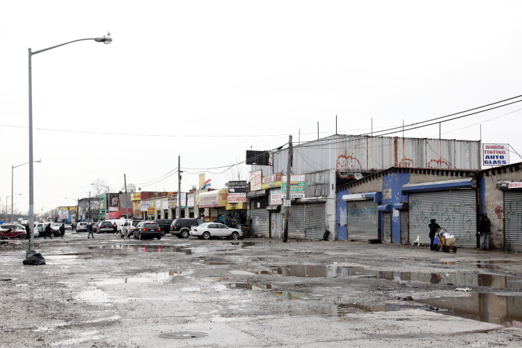 Roaming pushcart vendor and swamped roadway, Willets Point, Queens