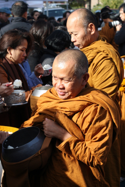 Monks receiving offerings of rice during the Royal Kathin Ceremony at Wat Buddhathai Thavorn Vanaram  Elmhurst  Queens