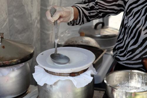 Spreading batter for steamed dumplings  @Nine  Experience Thailand  Union Square Park  Manhattan