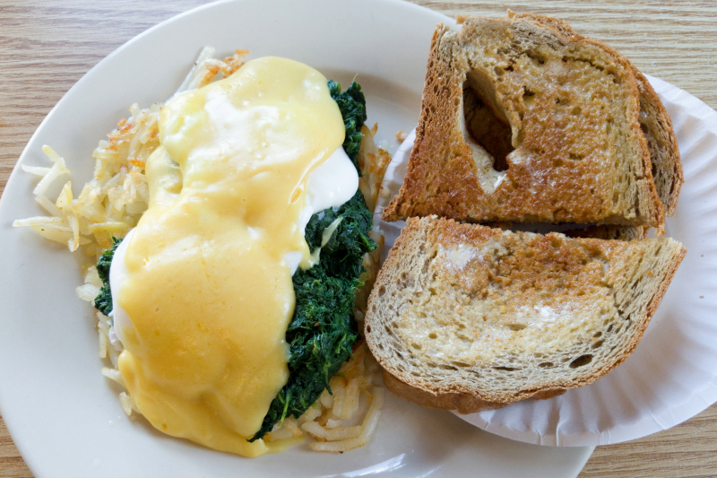 Eggs adrift (poached  with hollandaise sauce  over spinach and hash browns) with rye toast  Sandy Hook Diner  Sandy Hook  Connecticut