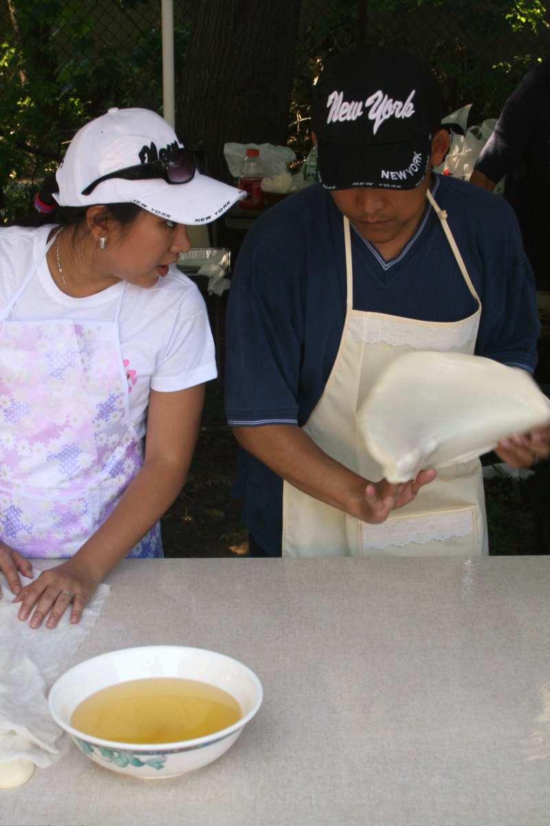 Flipping dough at the Myanmar Baptist Church Fun Fair  Briarwood  Queens