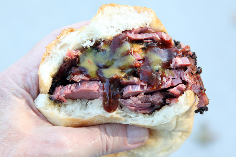 Pastrami sandwich (biteaway view) with spicy and mustard sauces    Red White & Que Smokehouse  Kearny  New Jersey
