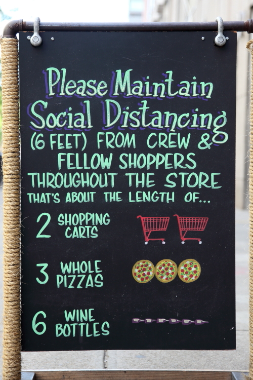 Please maintain social distancing  hand-drawn signboard  Trader Joe's Wine Shop  East 14th St  Manhattan