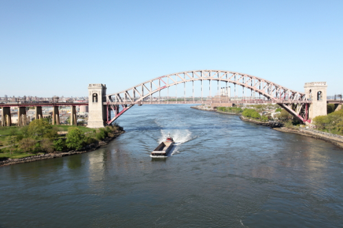 Barge and tug passing beneath the Hell Gate Bridge  connecting Randalls Island and Queens