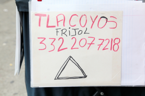Tlacoyos  frijol  hand-drawn sign (with illustration of a tetela) on a street vendor's handcart  East 116th St  Manhattan