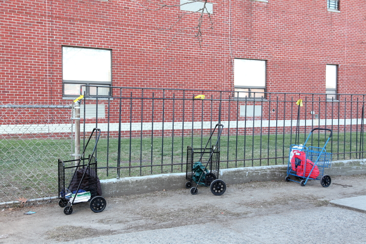 Pushcarts holding places in line for a parking-lot food pantry  The First Baptist Church  East Elmhurst  Queens