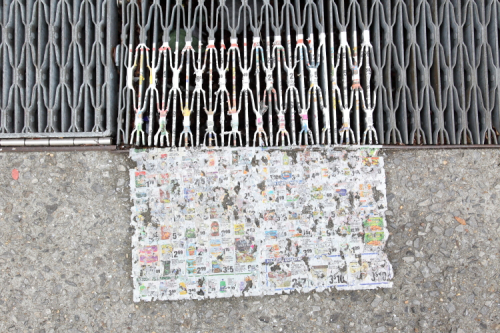 Weathered supermarket flyer on grating and sidewalk  Morrisania  Bronx