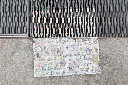 Weathered supermarket flyer on grating and sidewalk  Morrisania  Bronx